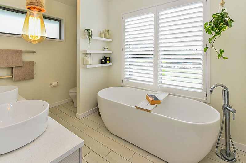 Large freestanding bath under large picture window with shutters and view. Double round basins with rope pendents