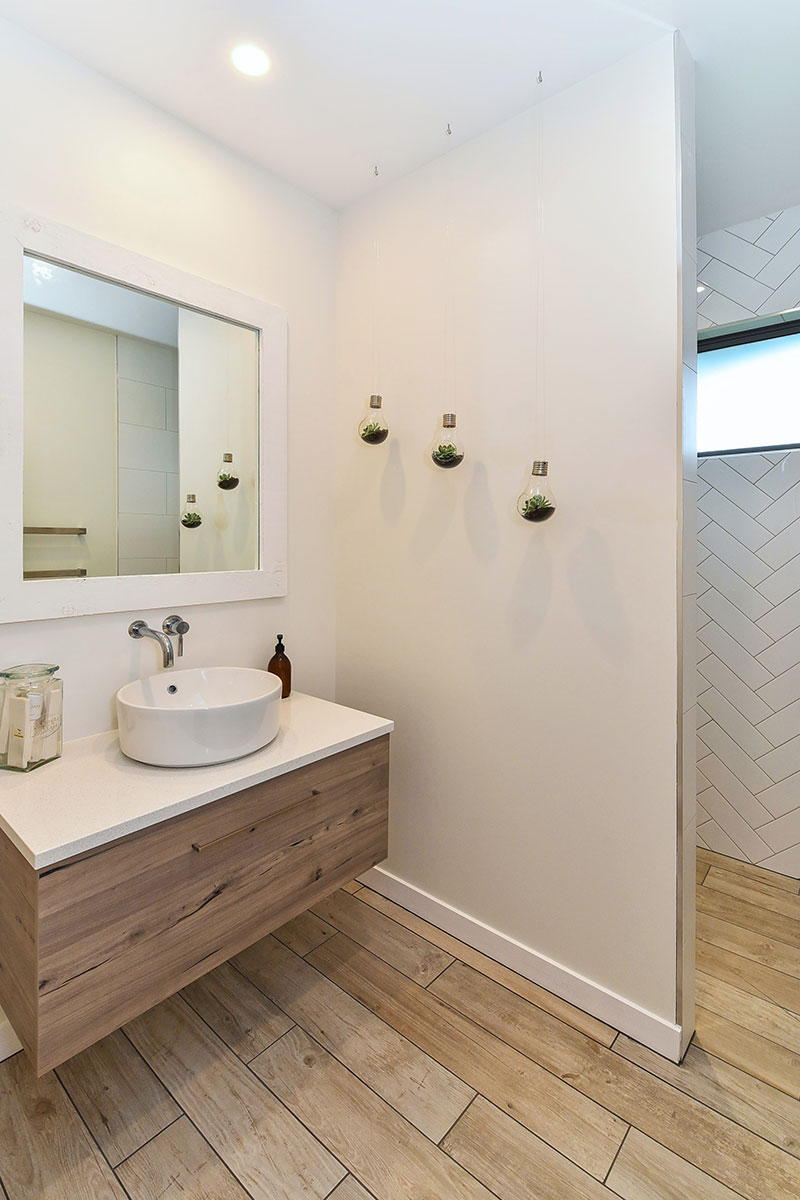 Guest Bathroom with wooden floor tiles, wooden vanity and herringbone style feature wall in shower