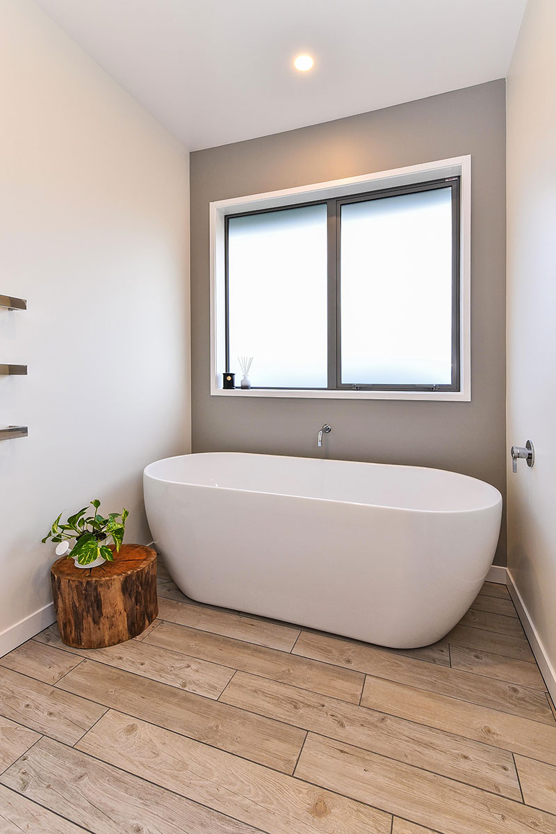 Large Free standing bath in front of grey feature wall with wooden floor tiles, large stump and plant
