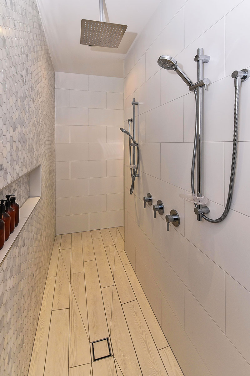 Large walk through double shower with marble mosaic feature wall, wooden floor tiles and rainhead
