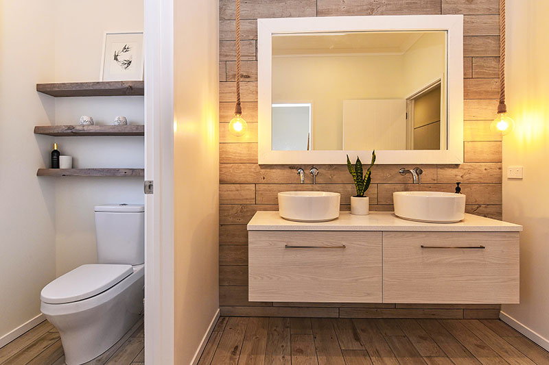 Wooden floor & wall tiles, light wood double vanity with round basins, hanging rope pendent lights & rustic shelves in toilet