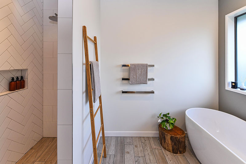 Shower with herringbone tile feature wall and wood floor tiles with freestanding bath, wooden ladder and stump decor