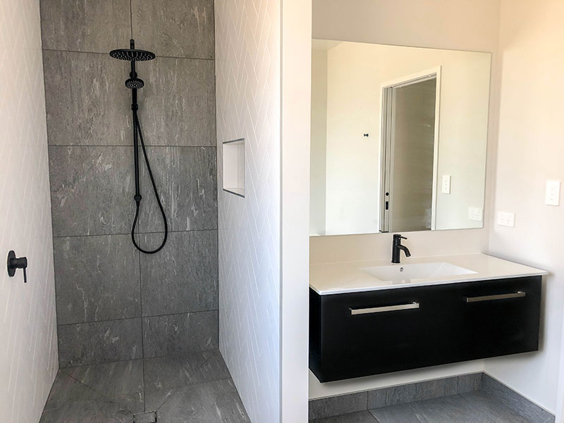 Black Elementi tapware and shower with grey tiled wall and floor, white subway herringbone and black vanity