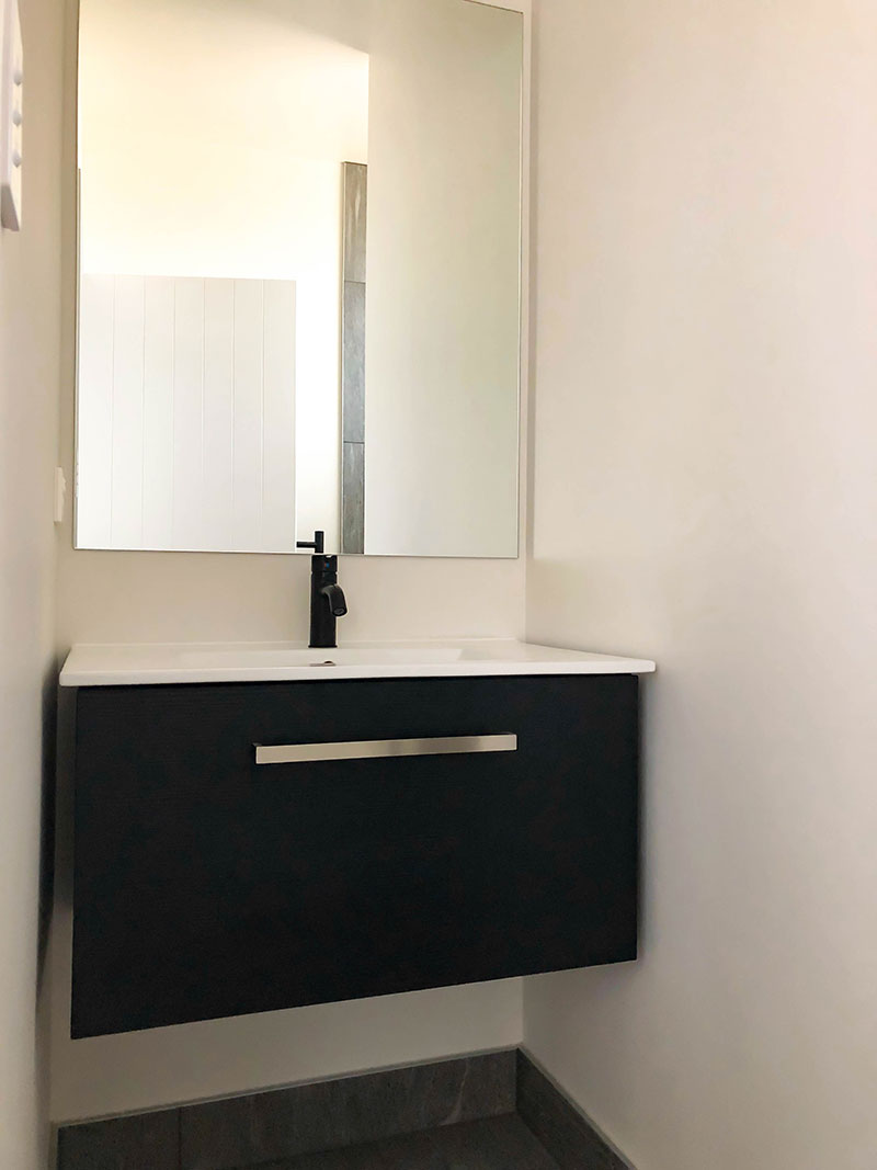 Black Elementi tapware and black vanity with white top, grey tiled floor