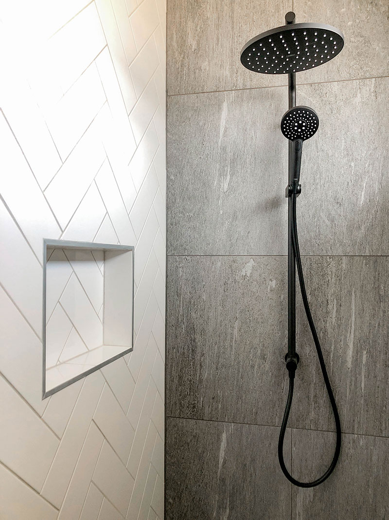 Black Elementi Shower Slide and dumper in shower with grey tiled wall and floor and white subway herringbone