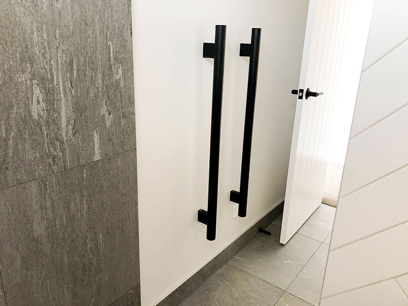 Black vertical heated towel rails with grey tiled wall and floor and white subway herringbone