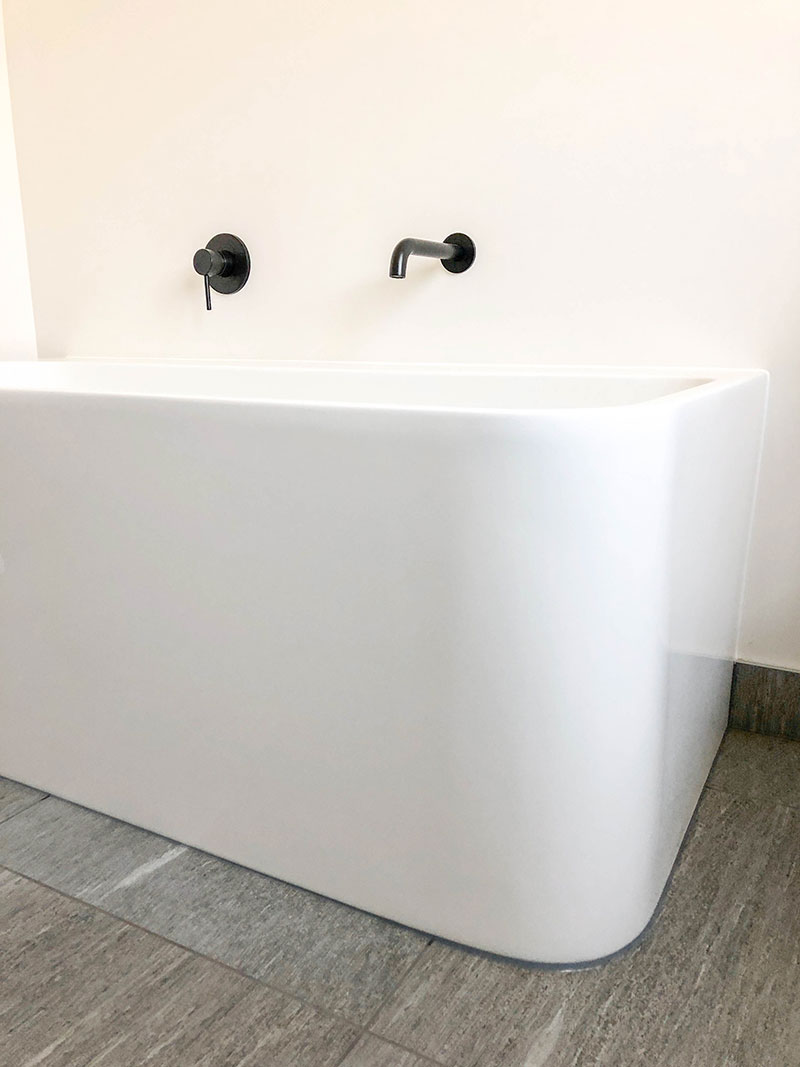 Black Elementi tapware with white freestanding 3 side bath and grey floor tiles