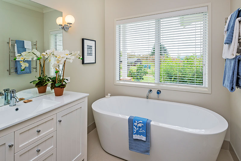 Traditional style vanity with free standing bath and blue accents in award winning home
