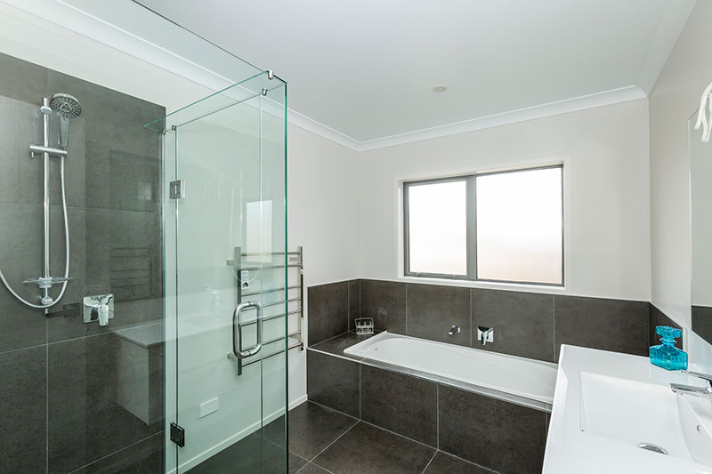 Simple bathroom design with grey brown tiles, in shower and around bath with glass shower frame