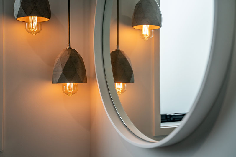 Concrete pendent lights lit up next to white round mirror in Precision Homes Paerata Rise Showhome.