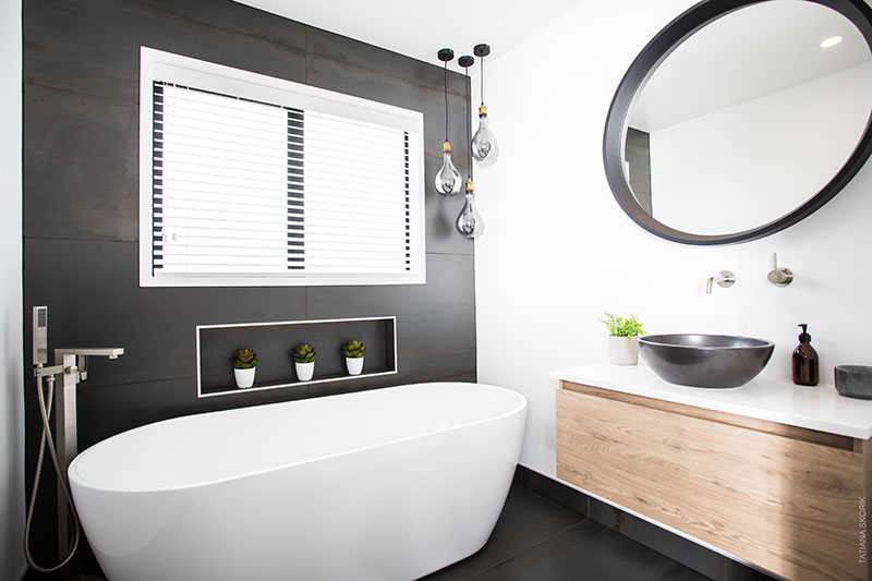 Showhome bathroom with freestanding bath, wooden vanity, feature pendent lights, charcoal basin and charcoal round mirror