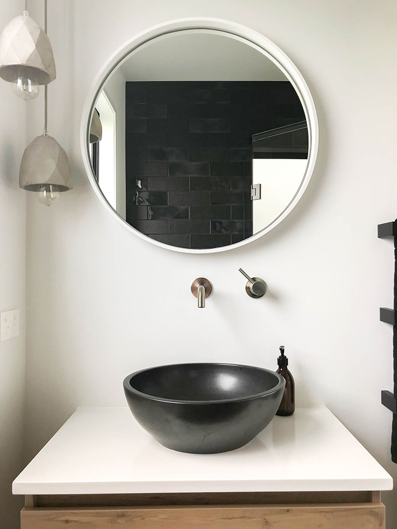 Timber vanity with charcoal basin, white round mirror, concrete pendent lights and charcoal subway tiles in shower