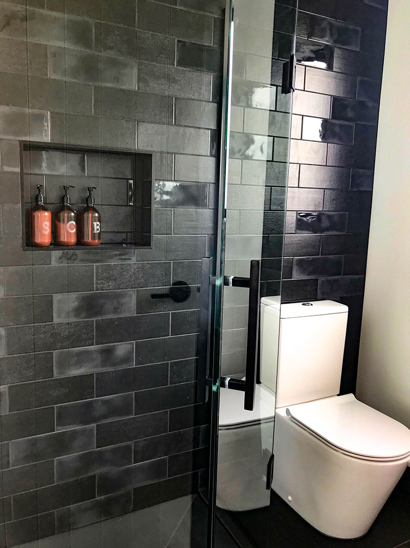 Charcoal / black diesel subway tiles on ensuite feature wall with recess shelf and glass shower frame with black details