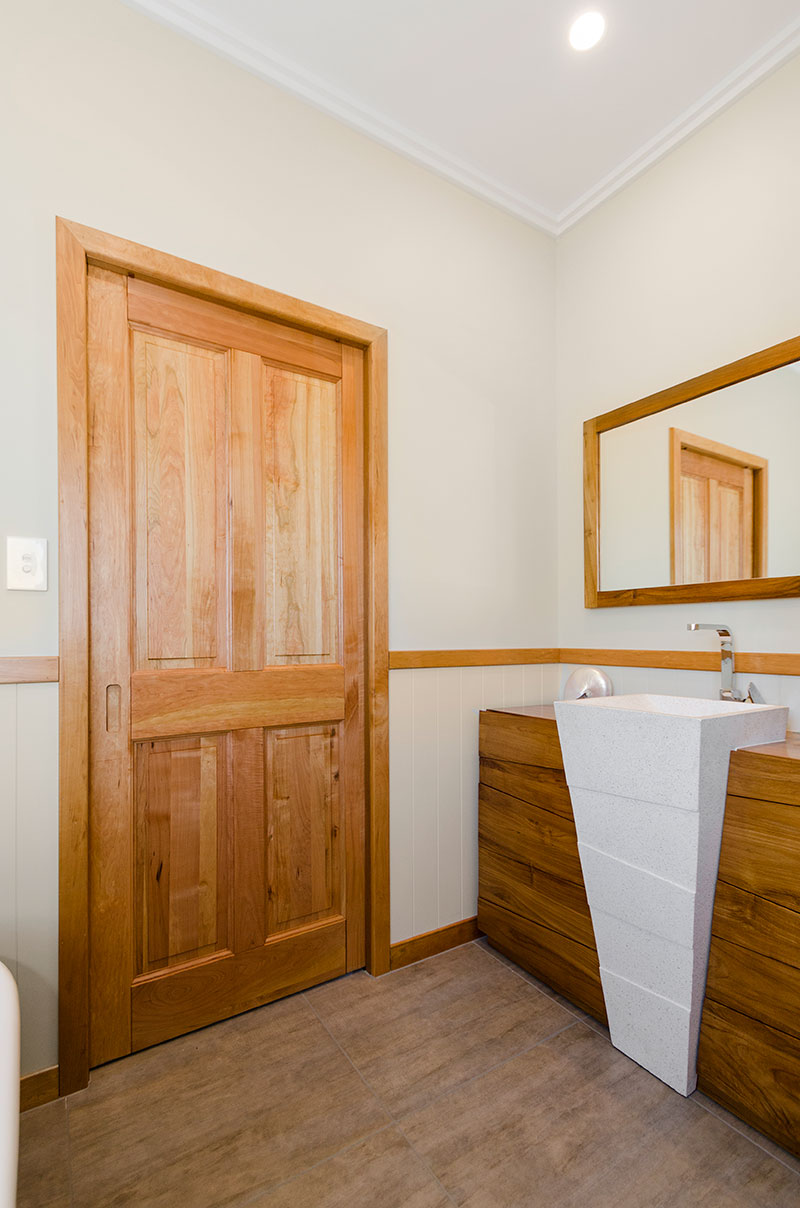 Unique wood and stone vanity in bathroom with timber accents of Award winning colonial home in Waiau Pa