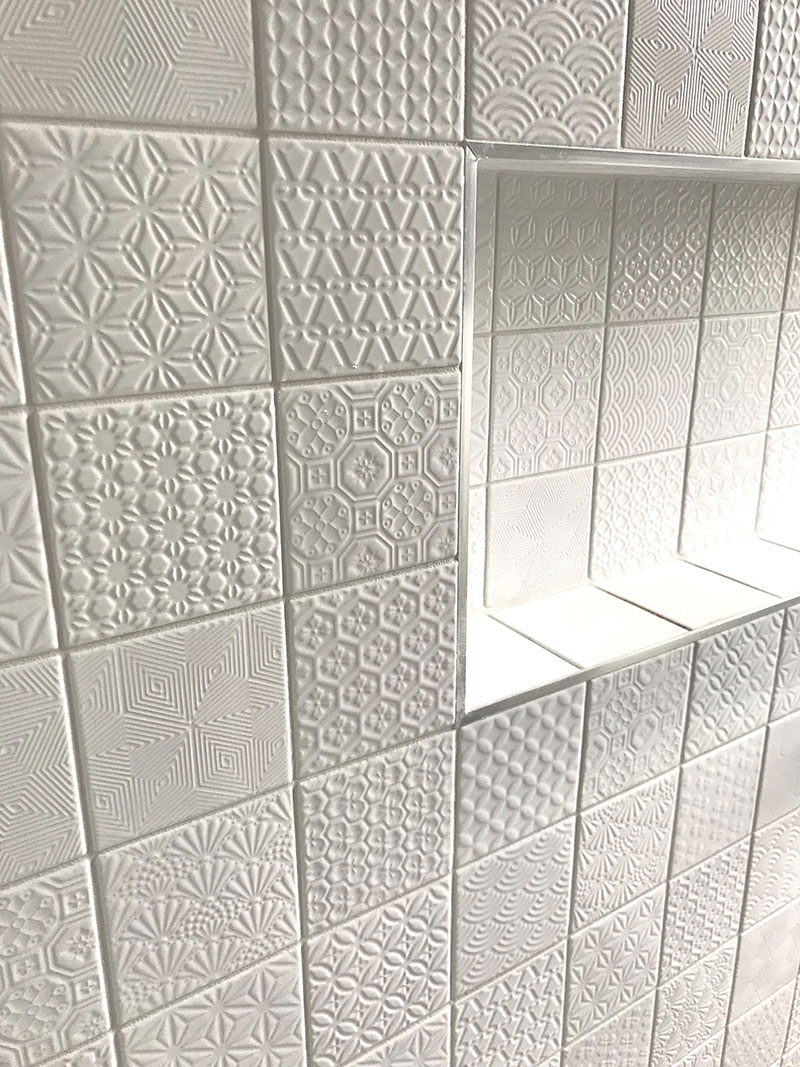 Close up of beautiful white, textured, patchwork style, mosaic tiles and recessed shelf