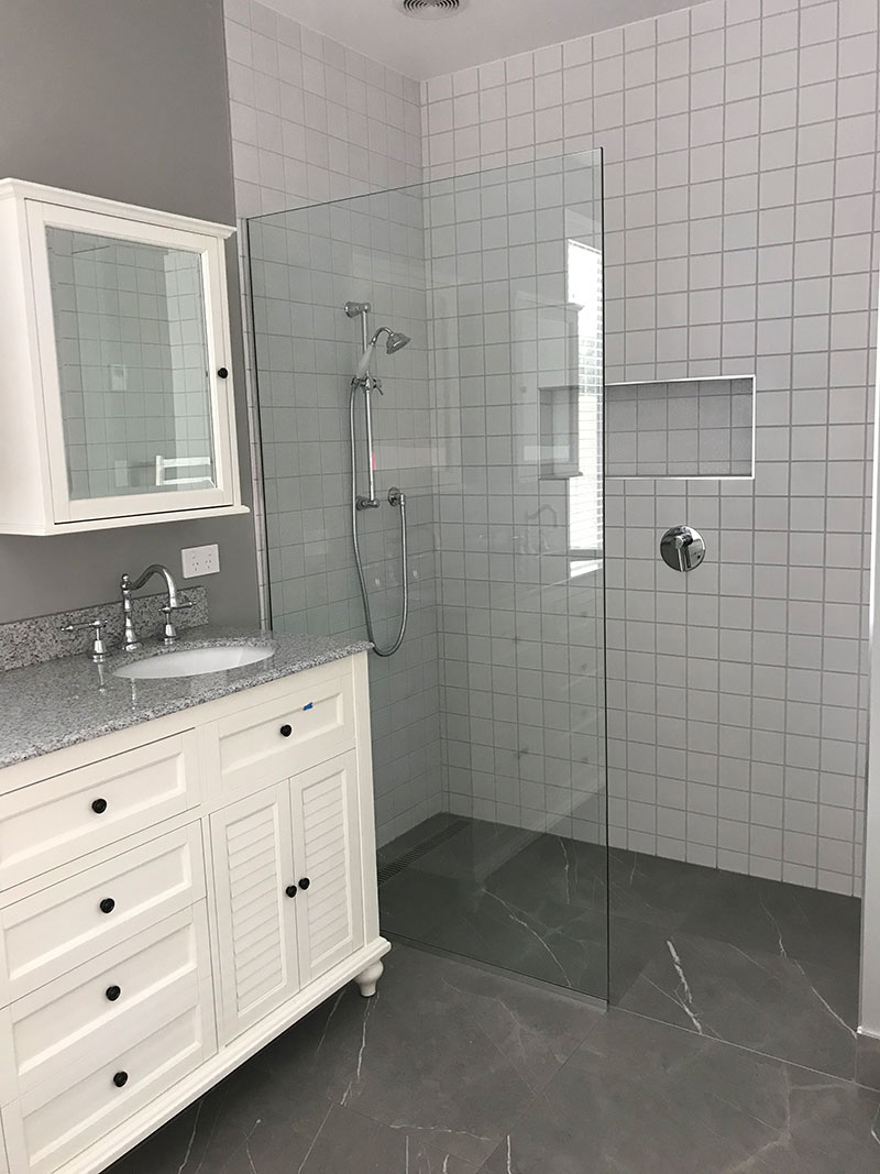 Traditional style vanity, tapware and cabinet with grey marble floor tiles. Large walk in shower with white patchwork wall tiles