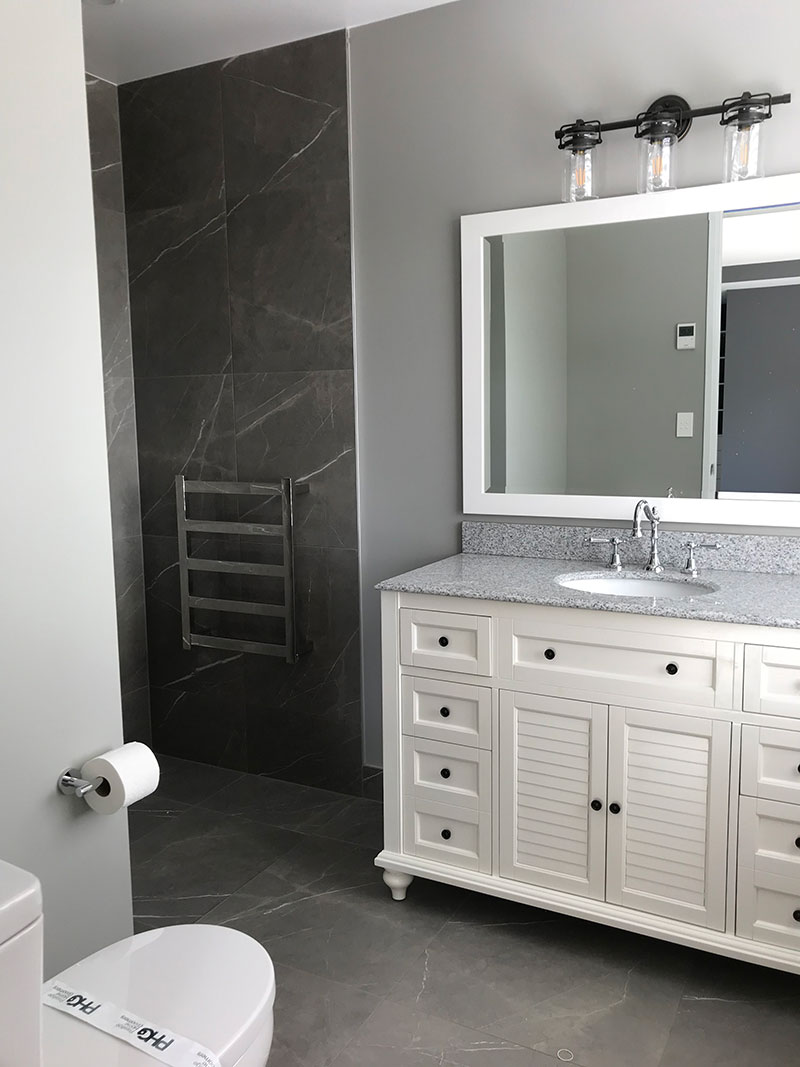 Colonial style vanity in ensuite bathroom with grey marble tiles on floor and shower walls.