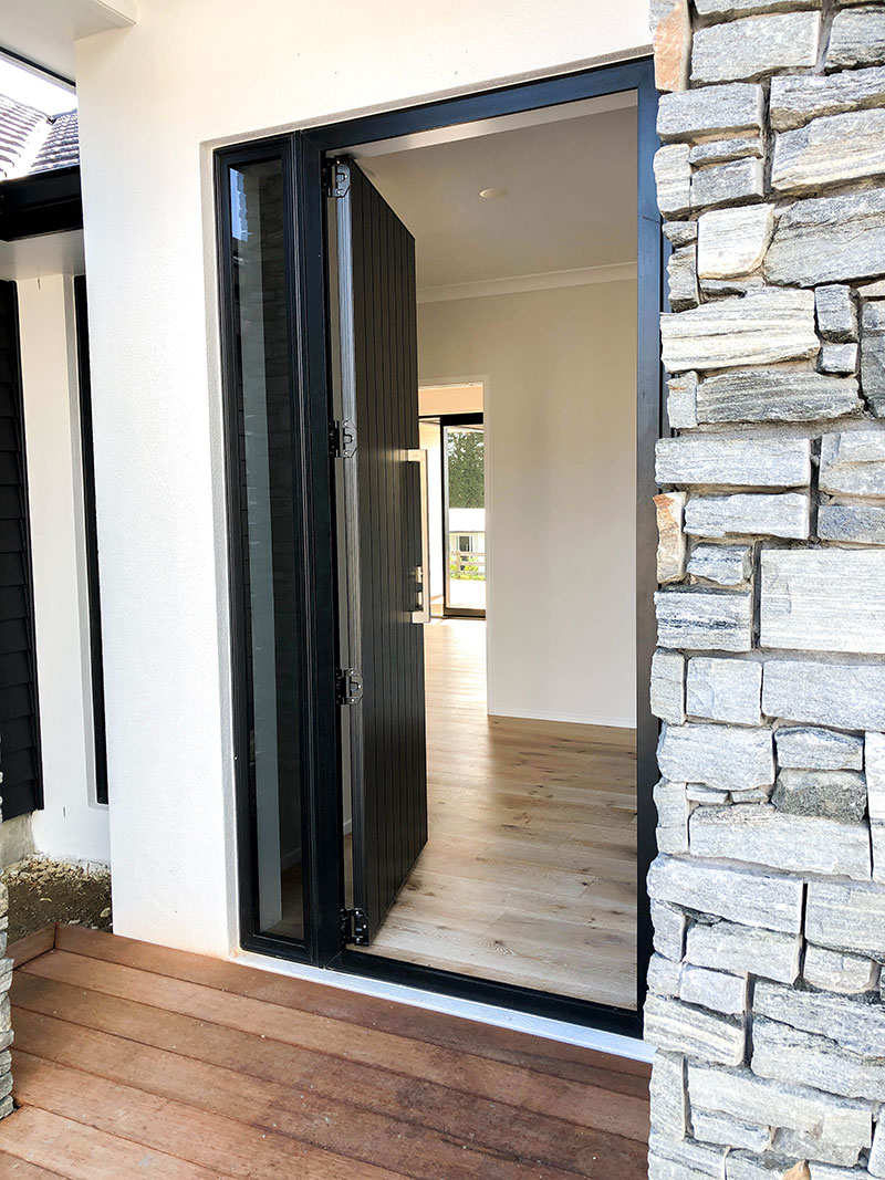 Entrance to new home with schist pillars, wooden deck, black front door and white plaster