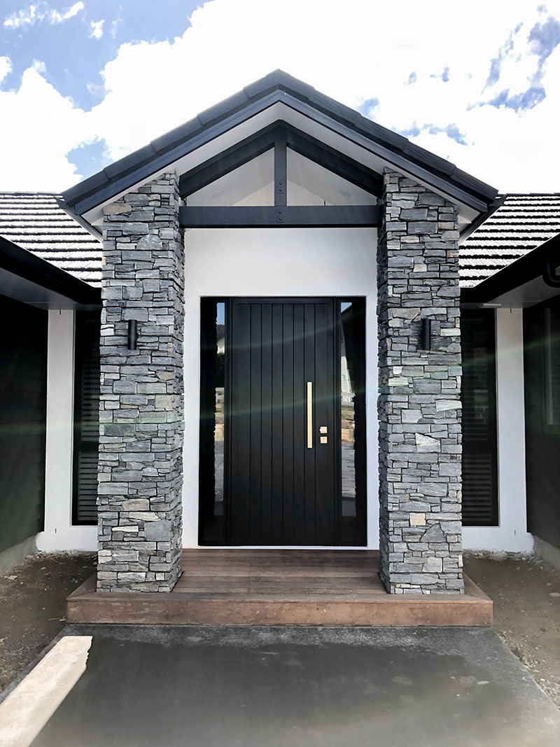 Entrance to new home with schist pillars, wooden deck, black front door, white plaster and black weatherboards