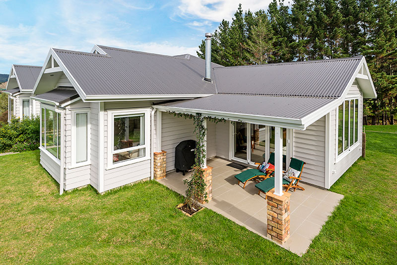 Colonial Style award winning home, clad in weatherboard with brick pillars surrounded by native bush