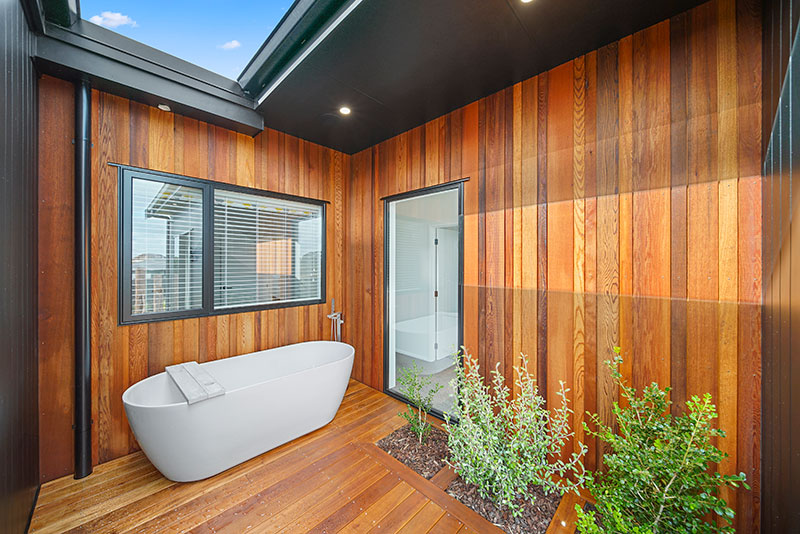 Stunning outdoor bath on deck at Paerata Rise Showhome. Cedar cladding and in deck planted shrubs