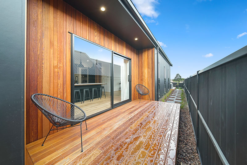 Exterior kitchen deck with black chairs with cedar clad wall and black fence