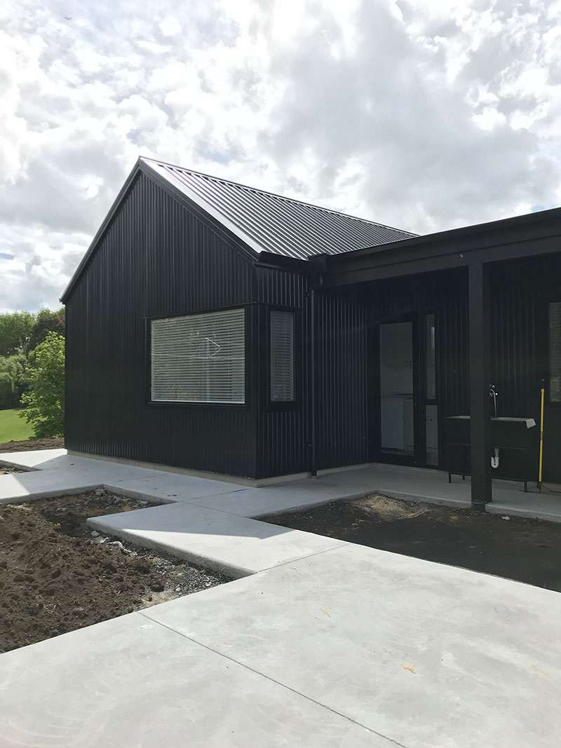 Exterior of black barn style house with path leading to laundry and back door