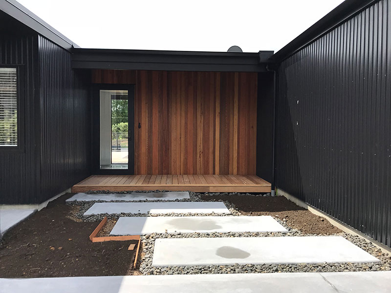 entrance to black barn style house with cedar feature and concrete slab path with stones