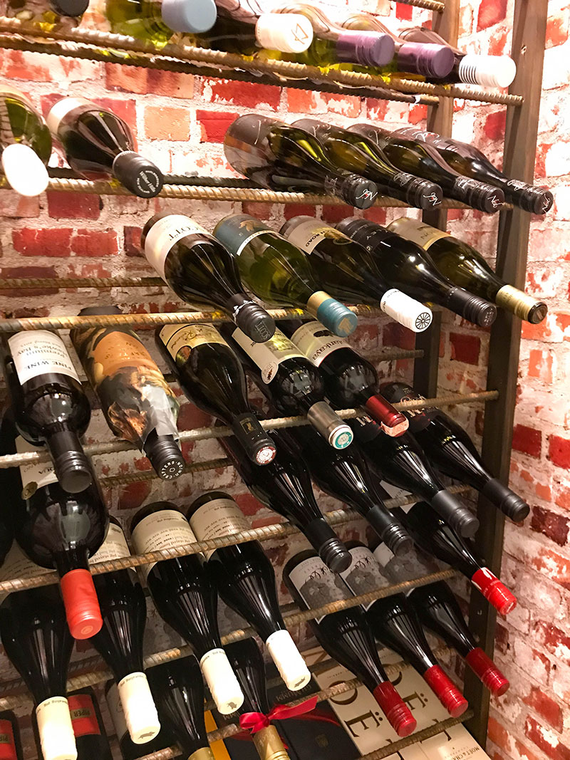 Stunning Wine cellar with bricked paper walls, and iron rods for shelving in award winning home