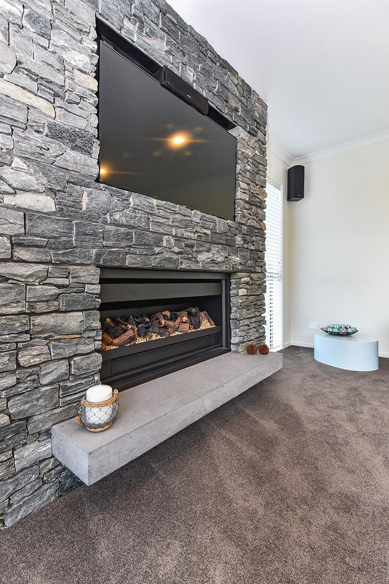 Beautful schist fireplace with recessed TV above and concrete hearth in award winning home