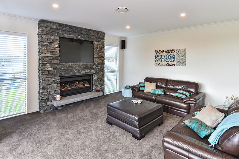 Large schist fireplace with TV in lounge with turquoise accents and concrete hearth