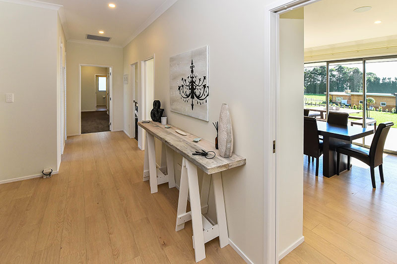 natural styled entrance and hallway. white and timber tones with trestle style hall table and wooden flooring