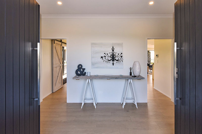 double door entrance into spacious, white & timber coastal / scandinavian style entry hall with trestle style hall table