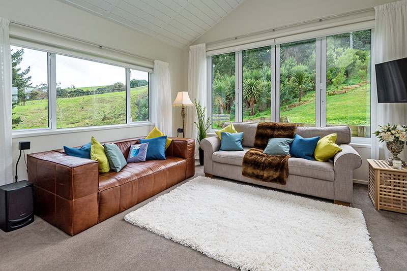 Beautiful airy lounge with high raking hardigroove ceilings. Leather and traditional couch with blue and green cushions
