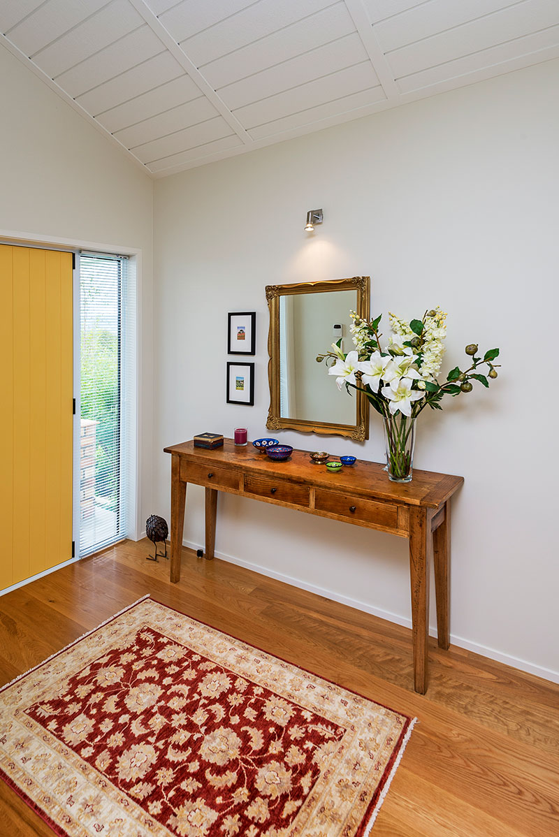 yellow front door in entry with raking, panelled ceilings and timber floor with rug