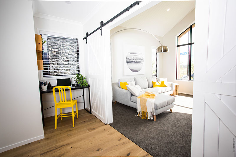 Lounge and study nook at Precision Homes Paerata Rise Showhome with grey yellow and black accents plus barn door