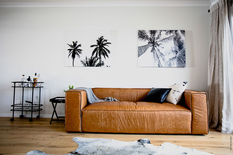 modern leather sofa on timber floor with drinks trolley and cow hide. brown and black accents
