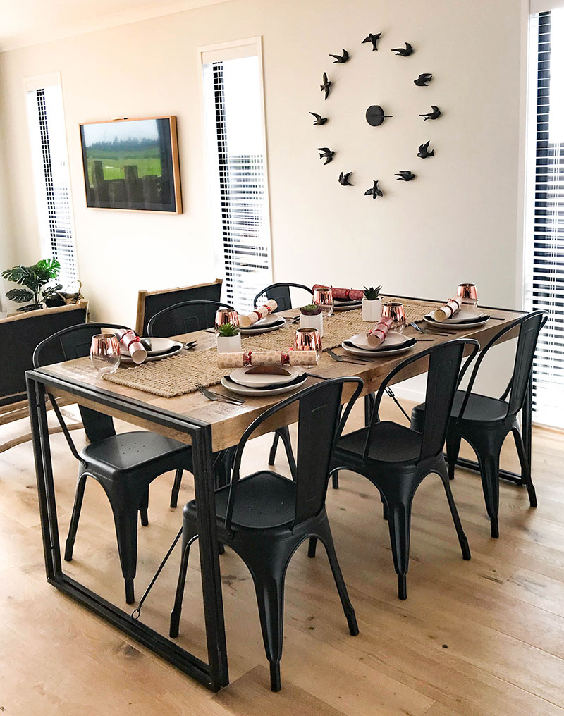 Rustic dining table with large bird wall clock in Paerata Rise showhome