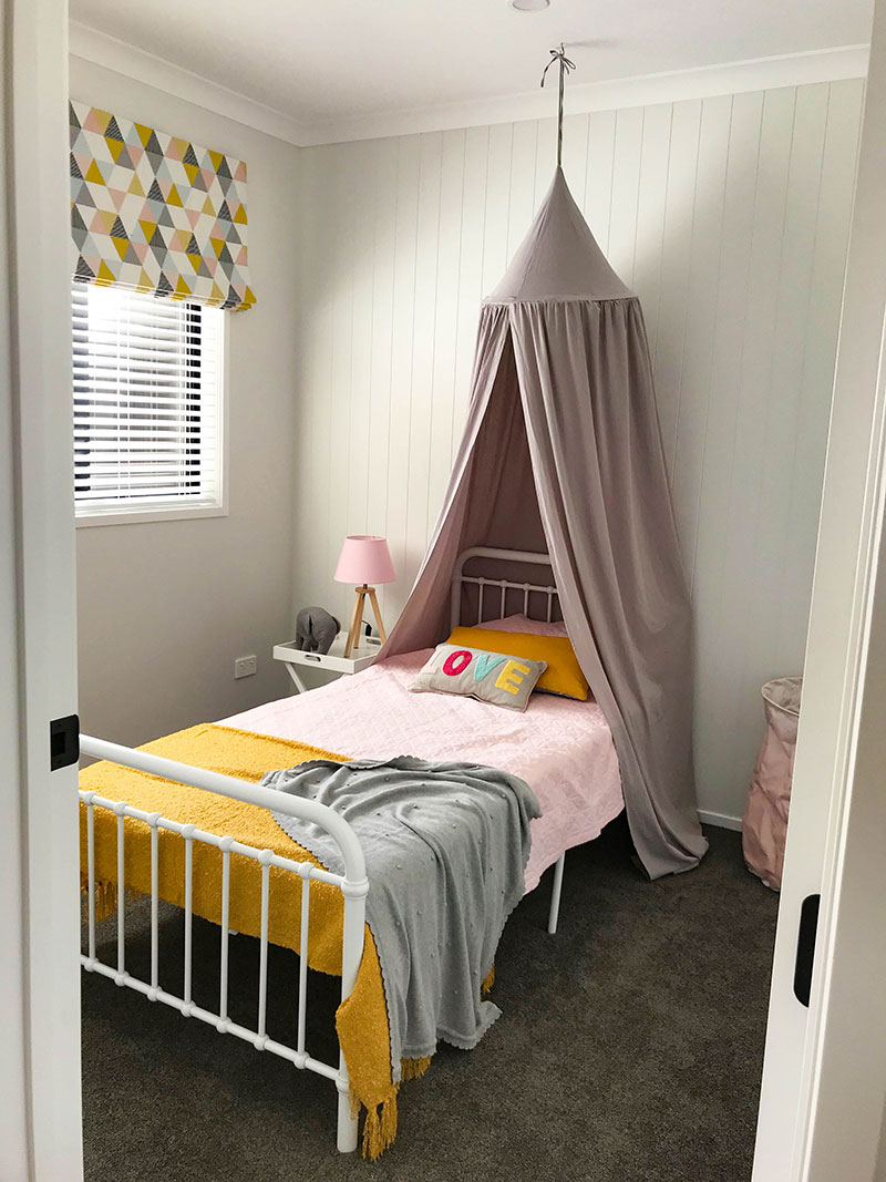 childrens bedroom with grey bed canopy pink, grey and yellow mustard geometric roman blind