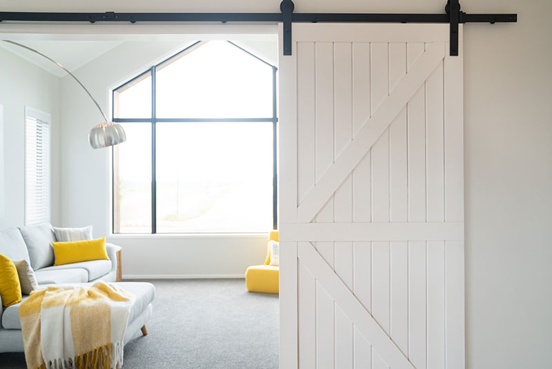 white rustic barn door with black runners on entrance to yellow and grey lounge