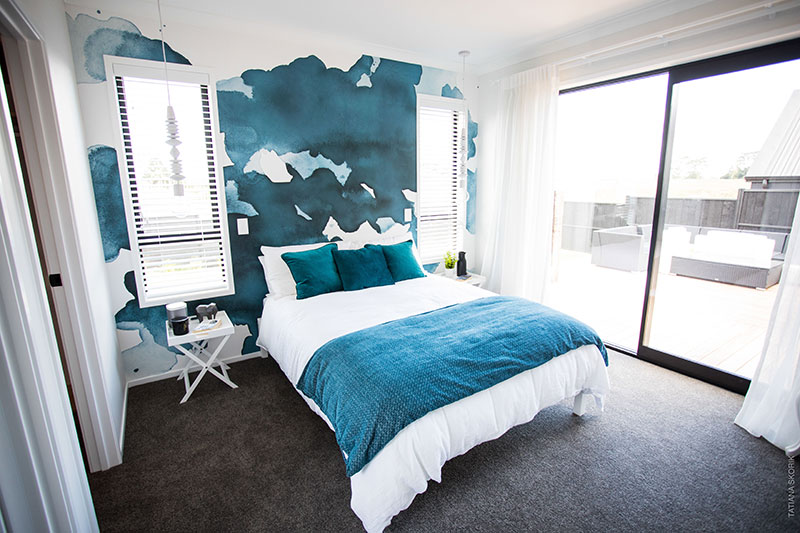 Fresh white and turquoise master bedroom with ink blot mural wallpaper, hanging lights and white blinds