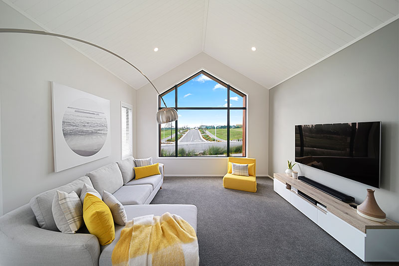 Yellow and grey lounge with lovely high arched window and raking ceilings with arco designer lamp