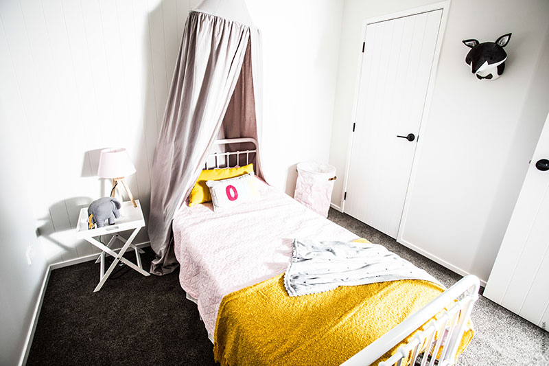 childs bedroom with canopy over bed, pink bed with yellow accents and metal bed frame