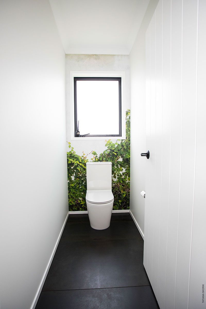 Toilet with dark charcoal tiles and mural wallpaper of ivy on concrete wall