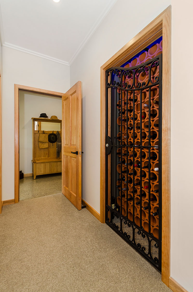 Wine cellar with wrought iron gate, terracotta pipe and wooden accents in award winning home