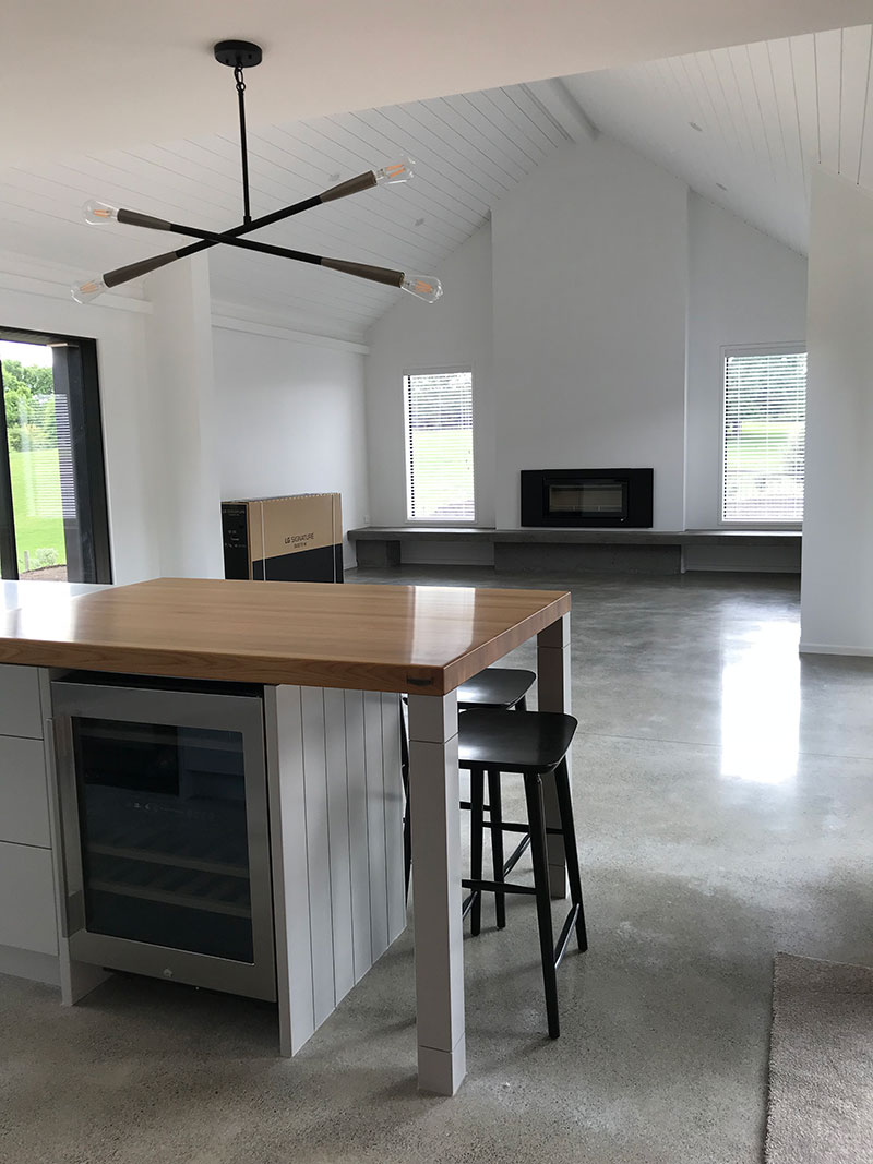 Timber bench, wine fridge and open plan living with polished concrete floor, sarked raking ceilings in hardigroove and fireplace