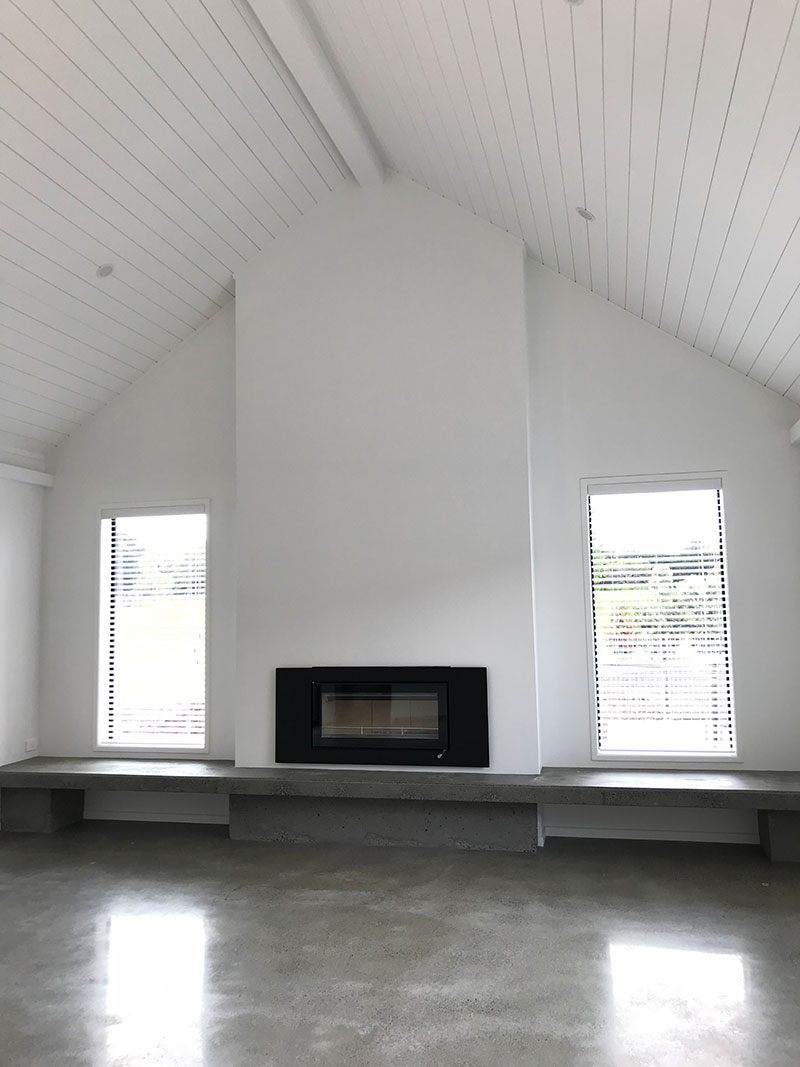 high stud sarked raking ceilings in hardigroove with fireplace with concrete hearth and polished concrete floor