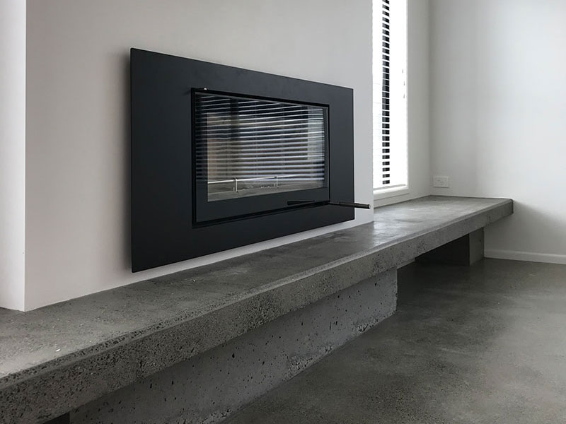 beautiful simple fireplace with concrete hearth seat bench with storage underneath and concrete floor