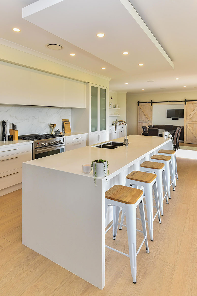 Light scandinavian style kitchen with white cabinets & benchtop, marble splashback & Timber floor.