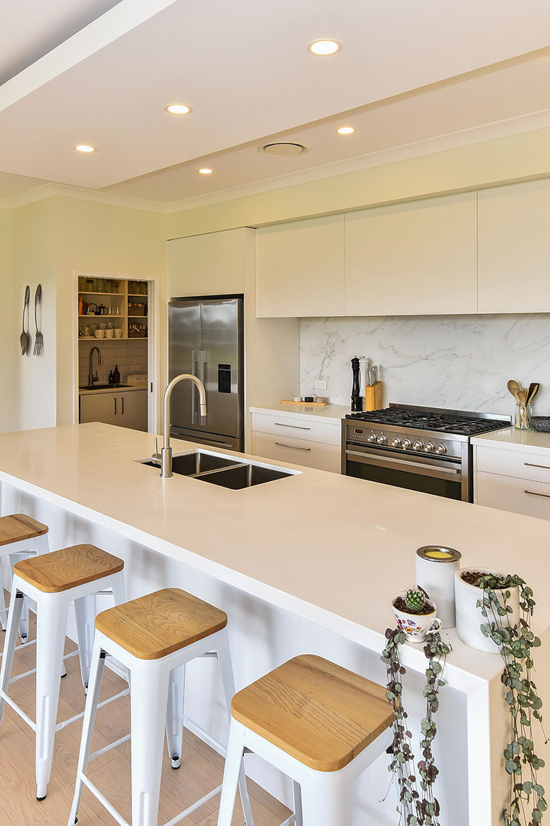 Light scandinavian style kitchen with white cabinets & benchtop, marble splashback and butlers pantry.
